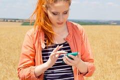 Mujer del pelirrojo que envía un mensaje que busca cobertura en el teléfono móvil fotografía de archivo