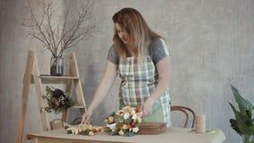Mujer del pelirrojo que hace el arreglo comestible en el lugar de trabajo almacen de metraje de vídeo