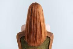 Mujer del pelirrojo que se sienta en la silla Foto de archivo libre de regalías