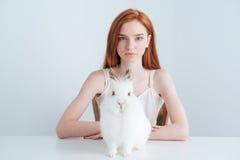 Mujer del pelirrojo que se sienta en la tabla con el conejo Fotografía de archivo
