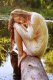 Mujer del pelirrojo que se sienta en una corteza de árbol cerca del río Imagen de archivo libre de regalías
