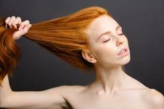 Mujer del pelirrojo que se sostiene el pelo sano y brillante, gris del estudio Imagen de archivo libre de regalías