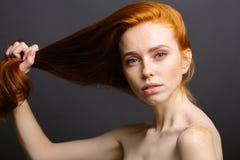 Mujer del pelirrojo que se sostiene el pelo sano y brillante, gris del estudio Fotos de archivo