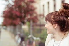 Mujer del pelirrojo que sonríe como ella espera en una calle Fotografía de archivo libre de regalías
