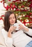 Mujer del pelo de Brown que se relaja con café en la Navidad Foto de archivo