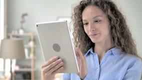 Mujer del pelo rizado que hojea en la tableta almacen de video