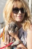 Mujer del pelo rubio con las gafas de sol que sostienen el conejito lindo del animal doméstico Imagen de archivo