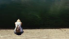 Mujer del pelo rubio que se sienta por el agua de río oscura, triste fotos de archivo libres de regalías
