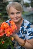 Mujer del pensionista con las rosas en jardín Imágenes de archivo libres de regalías