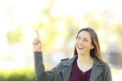 Mujer del presentador que señala arriba Foto de archivo libre de regalías