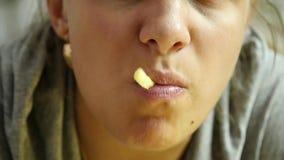Mujer del primer que come la comida basura con el gran disfrute la muchacha come las patatas fritas Cámara lenta almacen de metraje de vídeo