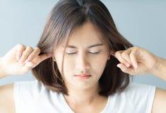 Mujer del primer que cubre los oídos con su mano, problema de ruido, foco selectivo foto de archivo