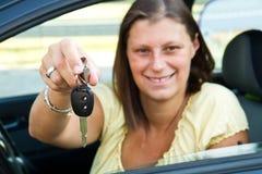 Mujer del programa piloto que sonríe mostrando nuevos claves del coche Foto de archivo