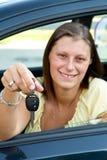 Mujer del programa piloto que sonríe mostrando nuevos claves del coche Imagen de archivo libre de regalías