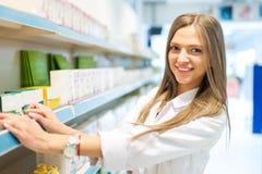 Mujer del químico del farmacéutico que se coloca en droguería de la farmacia