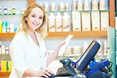 Mujer del químico del farmacéutico que trabaja en la caja registradora foto de archivo