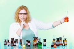 Mujer del químico con gesto del silencio de la cristalería aislada Imagen de archivo