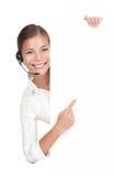 Mujer del receptor de cabeza en el centro de atención telefónica que se coloca en la cartelera Imagen de archivo libre de regalías