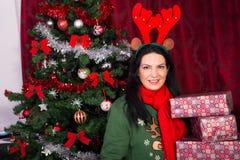Mujer del reno que sostiene los regalos de la Navidad Imagenes de archivo