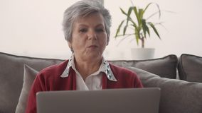 Mujer del retiro que disfruta de la comunicaci?n y que usa el ordenador port?til almacen de video