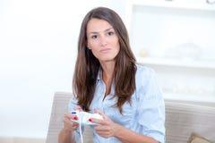 Mujer del retrato que juega a los videojuegos contra fondo gris Fotografía de archivo