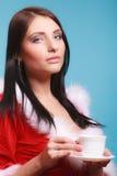Mujer del retrato que lleva el traje de Papá Noel con la taza de bebida caliente en azul Imagen de archivo libre de regalías