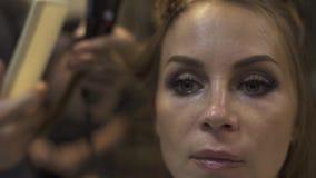 Mujer del retrato que recibe el pelo largo del peinado con hierro en estudio de la belleza Hairstyling usando las pinzas para end metrajes