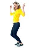 Mujer del salto de la cadera con los auriculares que disfruta de música Fotografía de archivo