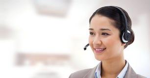 Mujer del servicio de atención al cliente con el fondo brillante en centro de atención telefónica foto de archivo