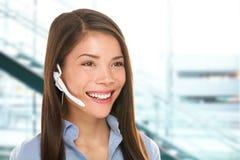 Mujer del servicio de atención al cliente de las auriculares en el centro de atención telefónica Fotografía de archivo