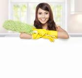 Mujer del servicio de la limpieza que presenta al tablero en blanco Imagenes de archivo