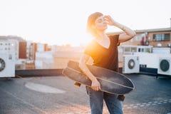 Mujer del skater con longboard en puesta del sol imagen de archivo libre de regalías