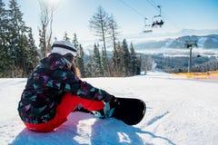 Mujer del Snowboarder que descansa sobre cuesta del esquí bajo elevación imagen de archivo libre de regalías