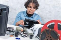 Mujer del técnico con el casete de VHS para la numeración imagenes de archivo