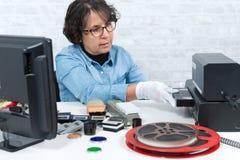 Mujer del técnico con el casete de VHS para la numeración imágenes de archivo libres de regalías