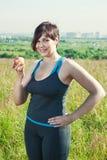 Mujer del tamaño extra grande de la aptitud con la manzana Imagen de archivo