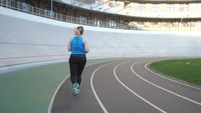 Mujer del tamaño extra grande durante la mañana que corre en pista metrajes
