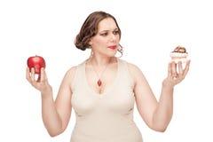 Mujer del tamaño extra grande que toma la decisión entre la manzana y los pasteles Fotos de archivo libres de regalías