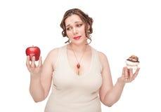 Mujer del tamaño extra grande que toma la decisión entre la manzana y los pasteles foto de archivo