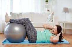 Mujer del tamaño extra grande que ejercita con la bola de la aptitud Foto de archivo libre de regalías