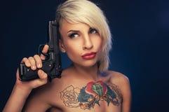 Mujer del tatuaje con un arma Foto de archivo libre de regalías