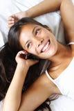 Mujer del teléfono en cama Foto de archivo libre de regalías