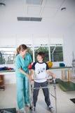 Mujer del terapeuta con el muchacho en la rehabilitación Foto de archivo libre de regalías