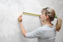 Mujer del trabajador que mide en straightedgetape de la pared Foto de archivo libre de regalías