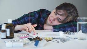 Mujer del trastorno con algunas píldoras en una tabla metrajes