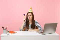 Mujer del trastorno en sombrero de la fiesta de cumpleaños con jugar el tubo que celebra solamente tomar ofensa mientras que sien imagen de archivo