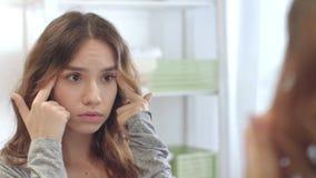 Mujer del trastorno que mira la cara y que toca el espejo del cuarto de baño del frente de la piel en hogar metrajes