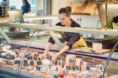 Mujer del vendedor de tienda que clasifica el queso en la exhibición del supermercado imagen de archivo libre de regalías