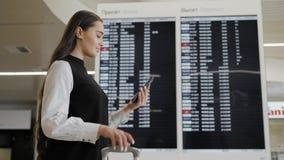 Mujer del viaje que usa smartphone en el aeropuerto Viajero caucásico joven que comprueba tiempo del embarque con el teléfono móv almacen de video