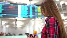 Mujer del viaje que usa smartphone en el aeropuerto Viajero caucásico joven que comprueba tiempo del embarque con el teléfono móv almacen de metraje de vídeo